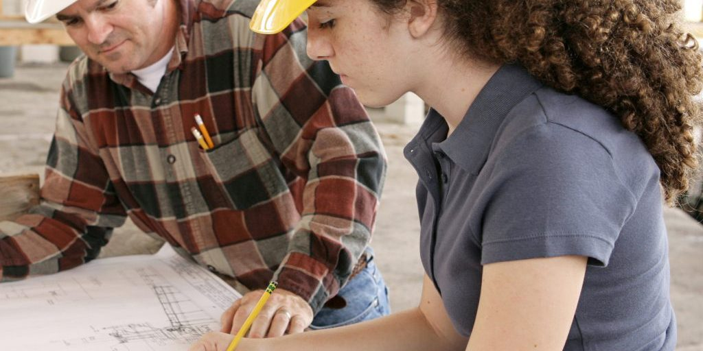 A female engineering student on a construction site marking blueprints as her instructor watches.